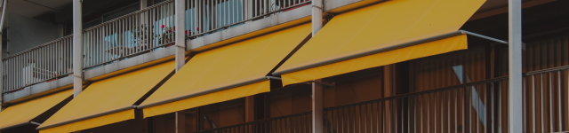 Nice balcony with yellow awning in apartment house.