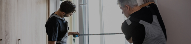 Two professional workers in uniform using tape measure while measuring window for installing blinds indoors. Construction and maintenance concept. Selective focus. Horizontal shot